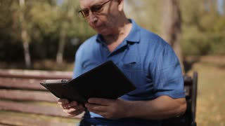An elderly man with glasses reading an e-book on a Park bench