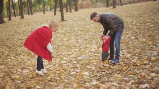 Beautiful family enjoying a walk in autumn day in the park. a small child learns to walk with his mother and father, parents help him to take the first steps