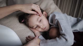 beautiful little girl on a sofa falls asleep and hugging a doll. Mom strokes a sleepy daughter