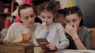 Beautiful mother with two daughters in cafe using phone and laughing