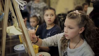 beautiful teenage girl sitting at the easel paints a picture in an art school. Professional art school for children