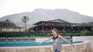 Beautiful young girl happy and has fun near the pool
