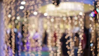 Bokeh of lights and garlands in the background dancing people
