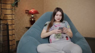 Cheerful pregnant woman using phone at home
