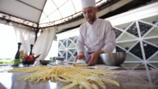 Chef prepares dough for making pasta, flouring the dough and kneading it