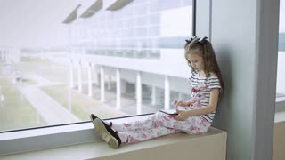 Child at the airport near the window playing a game on the tablet and waiting for time of flight