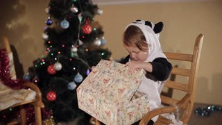 Christmas present with a surprise. Baby opens Christmas gift