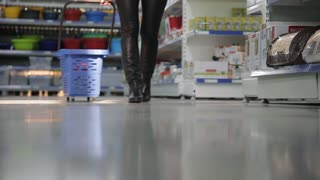 close-up of feet and girls with shopping trolley in a supermarket