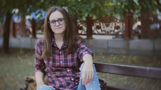 Close up of lovely middle-aged woman with glasses sitting on park bench smiling at camera.