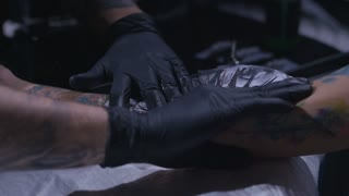 Close up shot of tattoo artist preparing skin of his client to the process of making tattoo in slow motion.