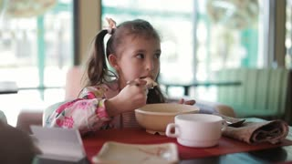 Closeup view of white cute little girl eating in restaurant with appetite.