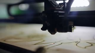 CNC machine cutting wood with a laser. CNC machine at work. Close-up.