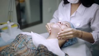 Cosmetologist medical gloves is touching girl's face. Woman is having cosmetic treatment at spa salon.
