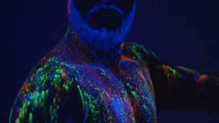 Dance in ultraviolet light. An unreal dance of a man in the ultraviolet light. Strong, muscular man is a stripper.