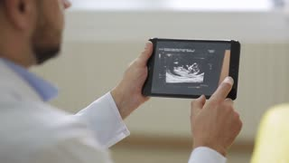 Doctor in white medical robe shows pictures of ultrasound to pregnant woman on a tablet