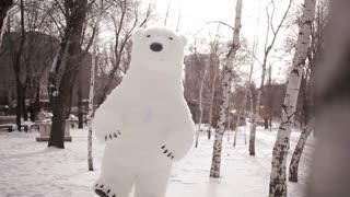 Doll giant bear dancing in a snowy park