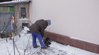 Elderly woman cleans the snow shovel near the house