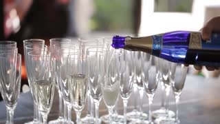 Elegant glasses with champagne standing in a row on serving table during the celebration. Waiters pouring champagne