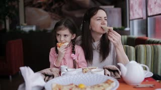 Family dinner at the pizzeria. Mother and daughter in the restaurant eating pizza