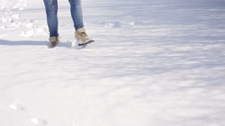 Female Legs Wearing Black Snow Boots Walking Though Fresh Snow On A Winter Day