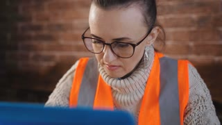 Focused woman Builder works with laptop and with the technical documentation in the room at the construction site.
