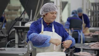 Food factory. Worker produces sausages on a automated food production equipment.