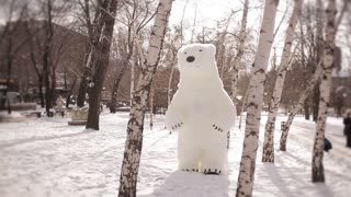 Giant puppets bear walks on a snow-covered birch forest. Puppets in the park