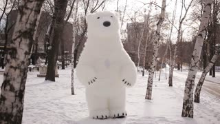 Giant puppets bear walks on a snow-covered birch forest