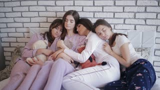 Group of girls after celebrating hen night sleeping together on the bed