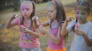 Group of kids playing together blowing bubbles having fun in a park, slow motion