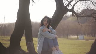 Guy approaches a lonely girl sitting on a tree in the park. The guy brings his girlfriend a blanket and tea