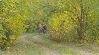 Happy children run home from school throwing backpacks up and catching them. Vacations in autumn. Slow Motion