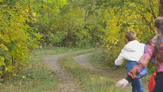 Happy children run through the autumn park, throwing backpacks up and catching them. Slow motion. Funny emotions on the faces of children