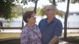 Happy elderly couple in love outdoor. Happy elderly seniors couple in sunny garden.