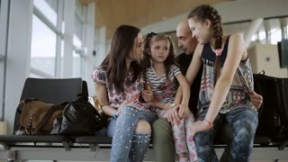 Happy family in the airport lounge waiting for your flight