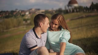 happy loving couple sitting face to face on green grass in park on city background