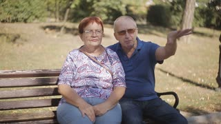 Happy retired couple enjoying each other s company dating in the park. Elderly couple on a Park bench