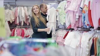 happy young family choose clothes for their unborn child. Pregnant woman in a store. Children's goods store