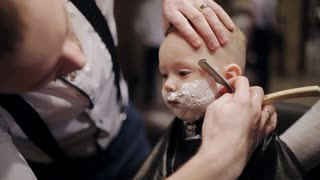 In a brutal men beauty salon a young child is shaved