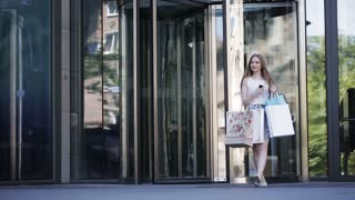 Lifestyle portrait young blonde girl, with shopping bags walking out from shop.
