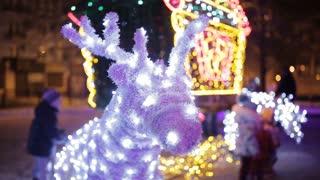 Lighted Santa Claus's reindeer against Christmas tree