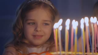 Little beautiful girl is blowing nine candles on the birthday cake in Slow motion. A happy little girl looks at the candles on a festive cake and makes her wish