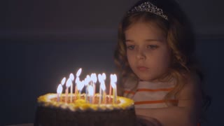 Little beautiful girl is blowing nine candles on the birthday cake in Slow motion