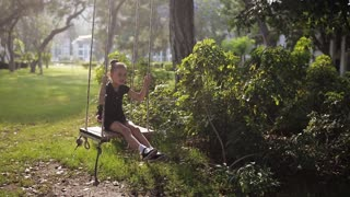 Little child girl have fun swaying on swing in nature forest park