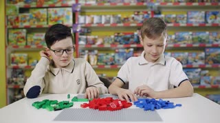 Little children playing with lots of colorful plastic blocks indoor,.