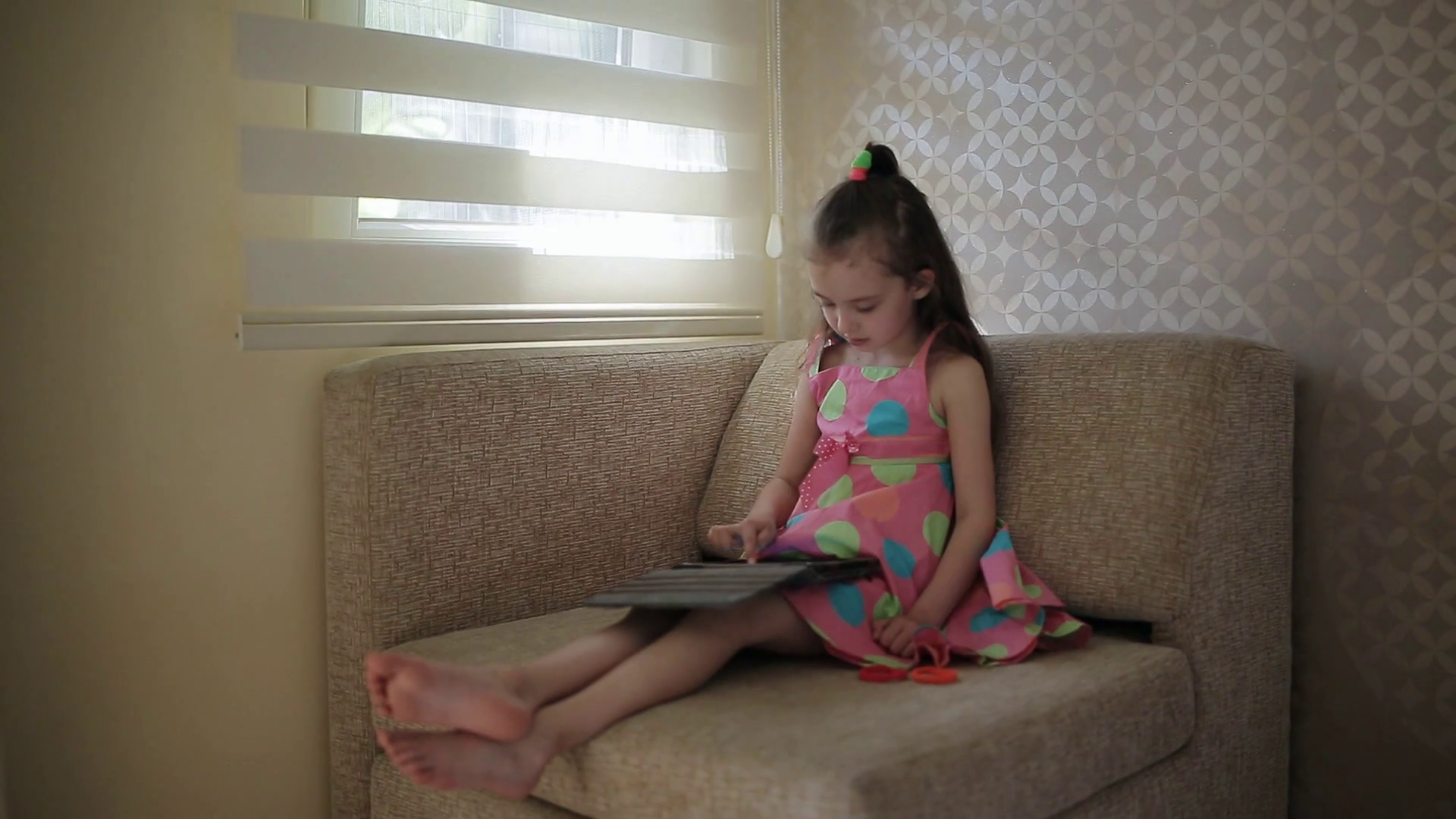 Little cute girl sitting on sofa and playing with tablet Stock Video Footage - Storyblocks