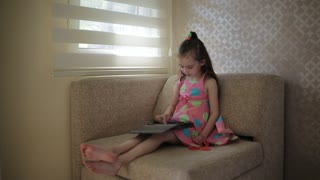 Little cute girl sitting on sofa and playing with tablet