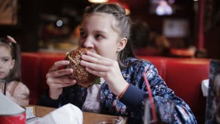 little girl eats a burger in fast food