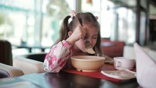 Little girl eats in the restaurant with an appetite