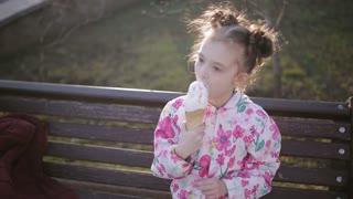 Little girl eats licks an ice cream cone on a park bench portrait